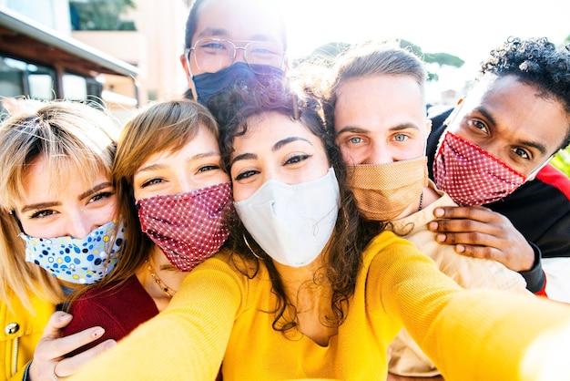 Amigos felizes usando máscaras protetoras tirando uma selfie nas férias