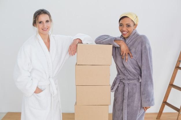 Amigos femininas em roupões de banho por caixas em casa nova