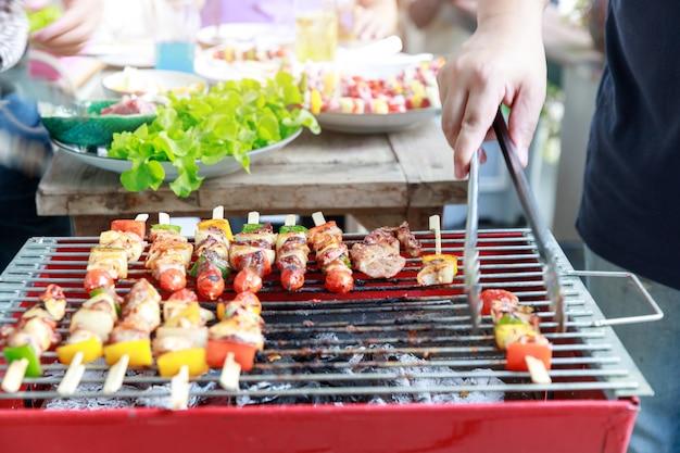 Amigos, festa e cozinhar churrasco em gardern.