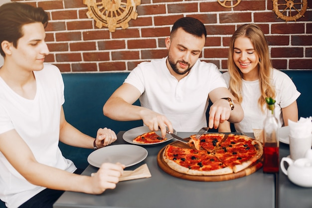 Amigos fofos em um café eatting uma pizza