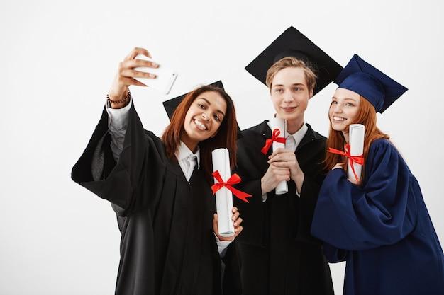 Amigos fofos graduados sorrindo segurando diplomas fazendo selfie.