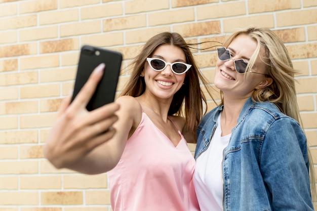 Amigos fofos tirando uma selfie juntos
