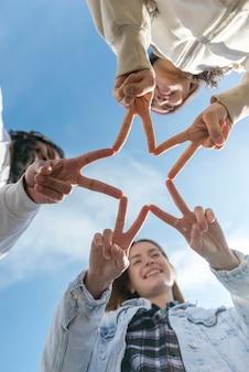 Amigos, formando uma estrela com os dedos