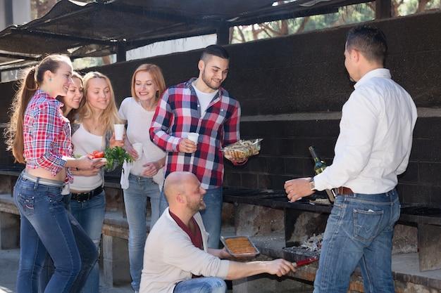 Amigos fritando carne ao ar livre