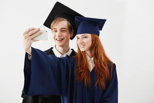 Amigos graduados da faculdade em caps sorrindo fazendo selfie.