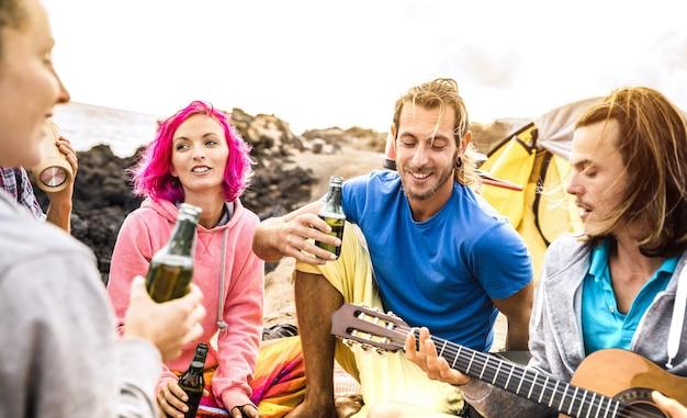 Amigos hipster se divertindo juntos em uma festa de acampamento na praia