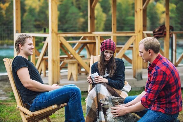 Amigos, homens e mulheres, jovens, felizes, bonito, quintal, falando, sentados em cadeiras de madeira