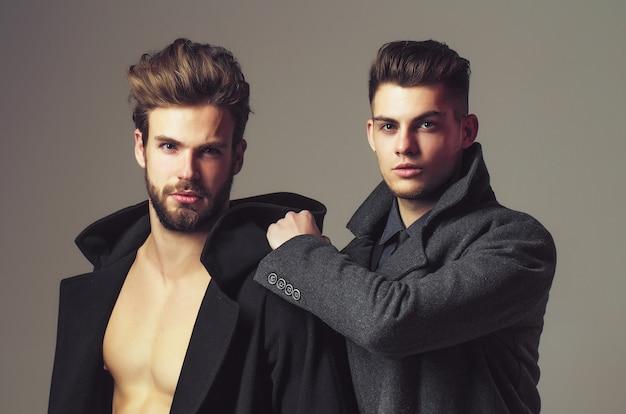 Amigos homens em casacos têm cabelo moderno e rosto sério em garotos cinzentos elegantes e sexy em estúdio com o torso nu
