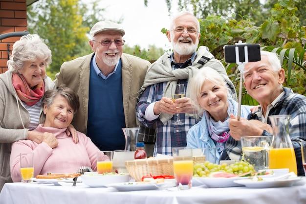 Amigos idosos felizes durante a festa no lindo jardim de uma villa suburbana