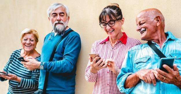 Amigos idosos felizes se divertindo com telefones inteligentes modernos - concentre-se na mulher com óculos