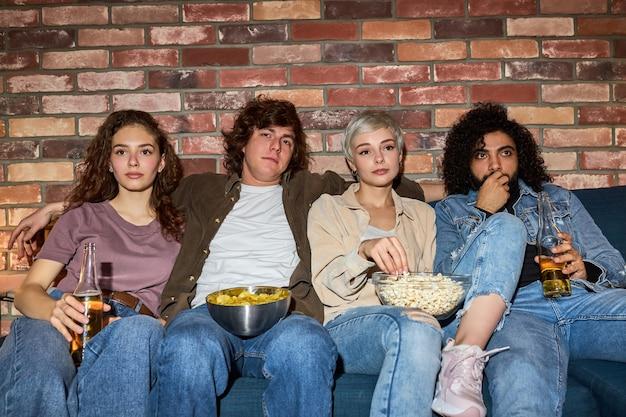 Amigos inter-raciais assistem a filmes juntos em casa à noite, comendo lanches e bebendo uma garrafa de cerveja, vestidos casualmente, passando os fins de semana juntos