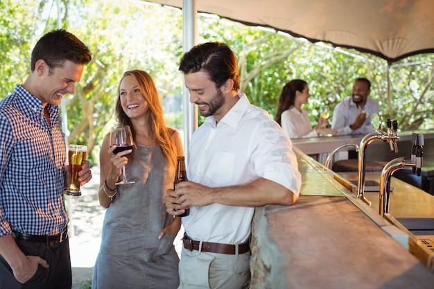 Amigos interagindo enquanto tomam uma bebida no balcão