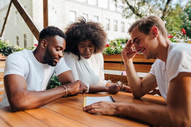 Amigos interculturais no restaurante, verificando o menu