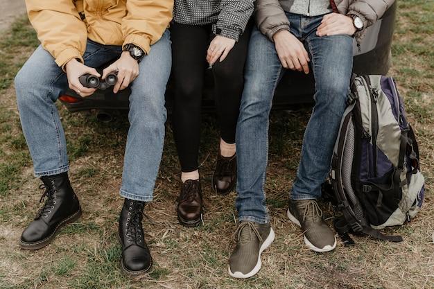 Amigos irreconhecíveis sentados juntos ao ar livre