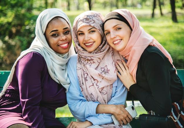 Amigos islâmicos sentado no parque e sorrindo para a câmera