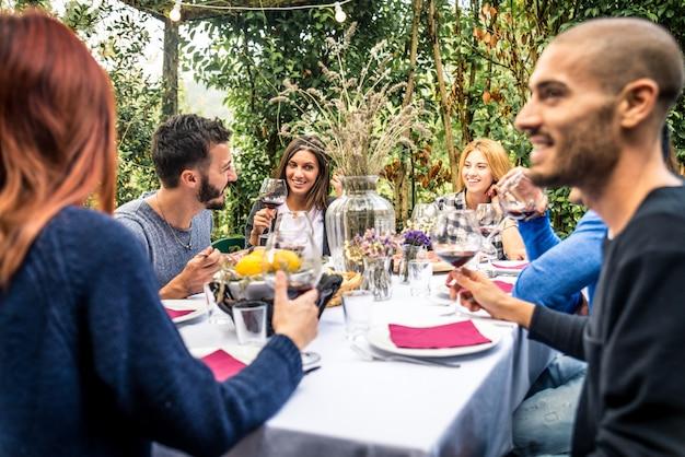 Amigos jantando no jardim