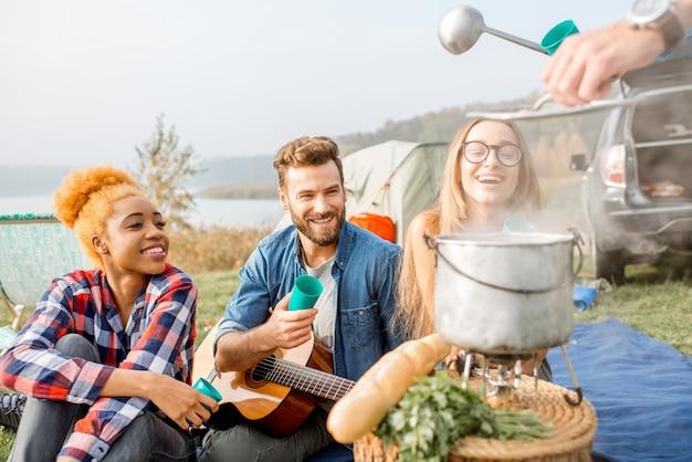 Amigos jantando saboroso com sopa cozida no caldeirão durante piquenique no acampamento