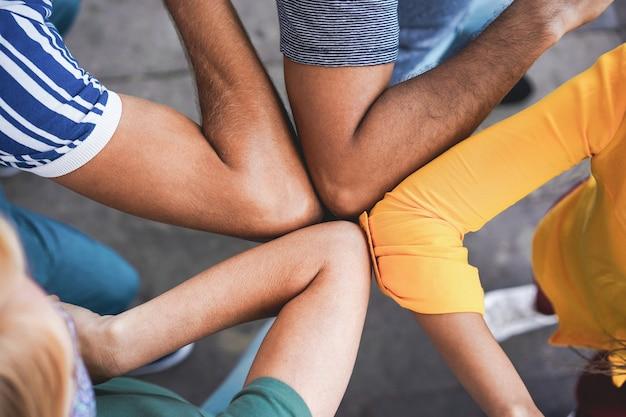Amigos jovens batem com os cotovelos em vez de cumprimentá-los com um abraço - evite a propagação do coronavírus, distância social e conceito de amizade - foco principal no braço esquerdo