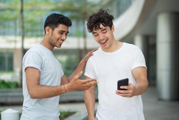 Amigos jovens emocionais, discutindo notícias chocadas