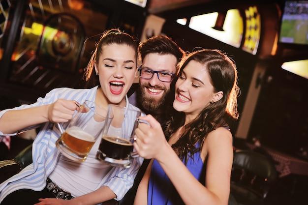Amigos - jovens rapazes e raparigas bebendo cerveja, conversando e sorrindo no bar