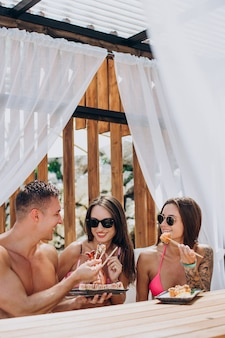 Amigos juntos comendo rolinhos de sushi à beira da piscina