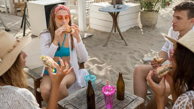 Amigos juntos na praia comendo hambúrgueres