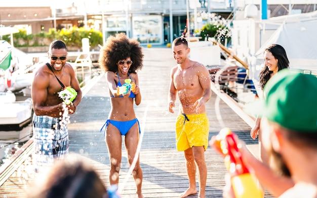 Amigos loucos e felizes se divertindo genuinamente com a batalha aquática no local de verão - conceito alternativo de férias com meninos e meninas usando pistola d'água nas docas da praia