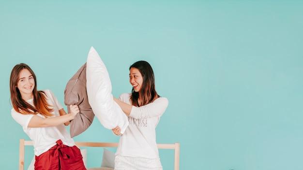 Amigos lutando com travesseiros na cama