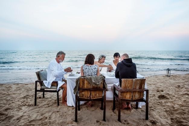 Amigos maduros, tendo um jantar na praia