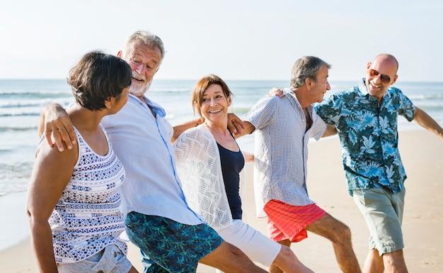 Amigos mais velhos brincando na praia
