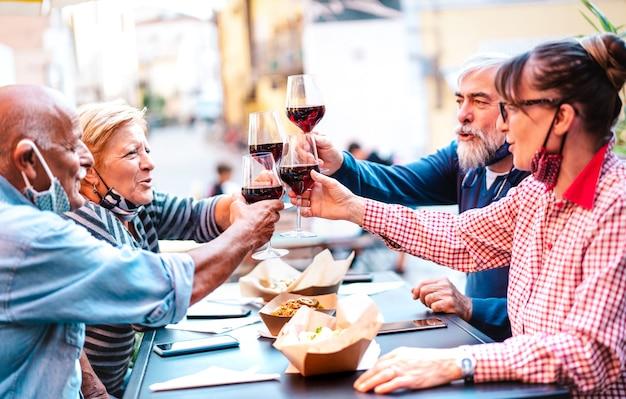 Amigos mais velhos brindando vinho tinto no bar da vinícola dehor com máscara aberta