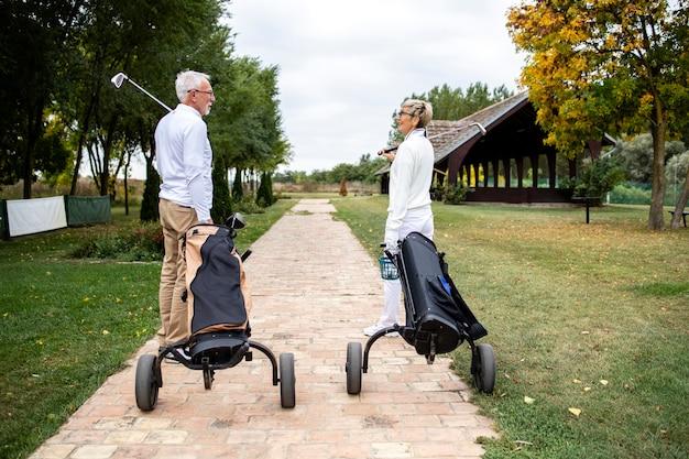 Amigos mais velhos com equipamento de golfe caminhando para o campo para começar a jogar golfe.