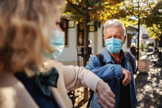 Amigos mais velhos com máscaras em pé ao ar livre e cumprimentam com os cotovelos.