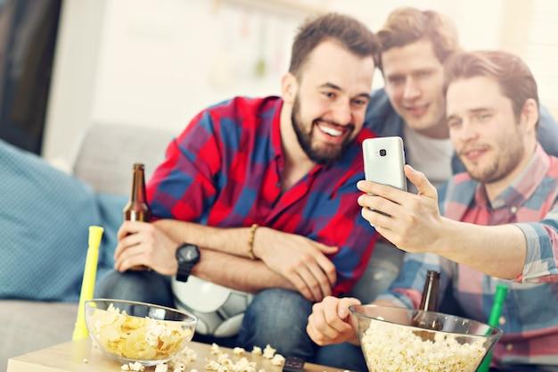 Amigos masculinos felizes torcendo e assistindo esportes na tv