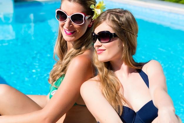 Amigos menina, bronzeando-se, em, piscina, frente, água