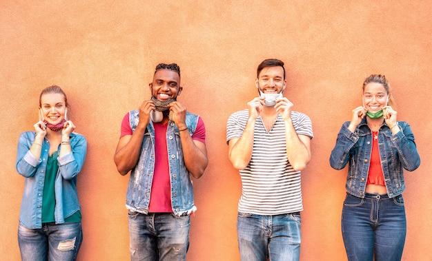 Amigos milenares multirraciais sorrindo com máscara facial após reabertura do bloqueio