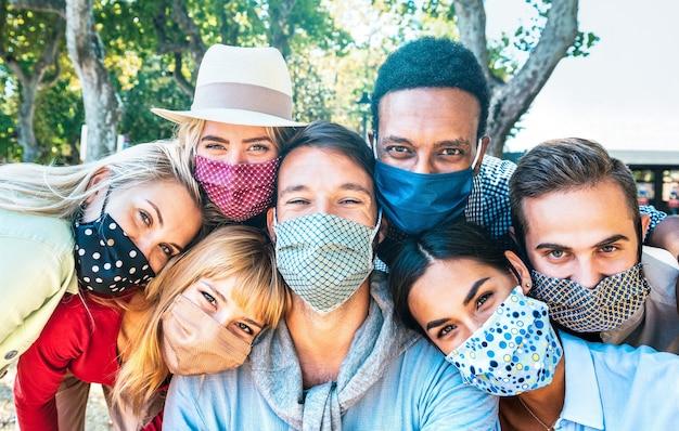 Amigos milenares multirraciais tirando selfie com máscaras faciais fechadas durante o surto da segunda onda de covid