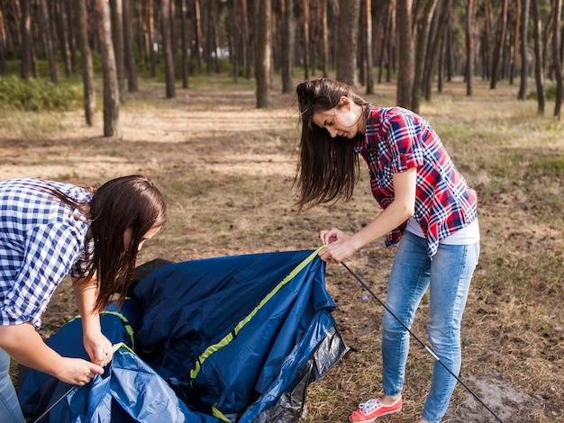 Amigos montam uma barraca juntos para descansar no acampamento. estilo de vida do turista. salve um amigo, ajude a apoiar o conceito de trabalho em equipe