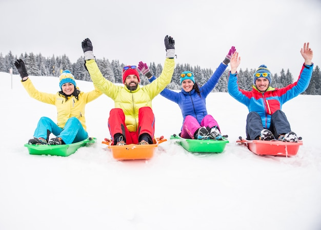 Amigos, montando trenós de neve