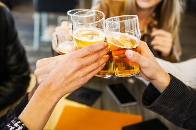 Amigos mostrando as mãos segurando copos de cerveja e torcendo uns com os outros