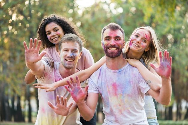 Amigos, mostrando as palmas das mãos coloridas no holi