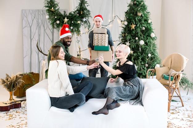 Amigos multiculturais brindando com champanhe enquanto um menino caucasiano segurando caixas de presentes