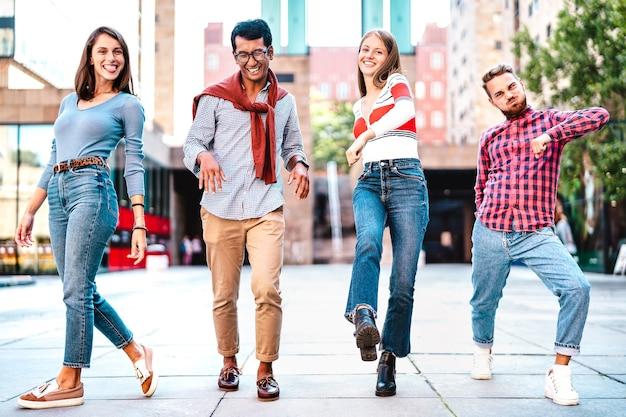 Amigos multiculturais caminhando pelo centro da cidade fazendo movimentos malucos engraçados