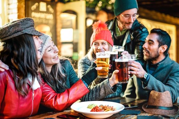 Amigos multiculturais felizes bebendo cerveja com nachos ao ar livre à noite