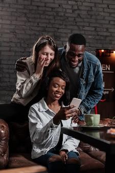 Amigos multiculturais, olhando para o telefone