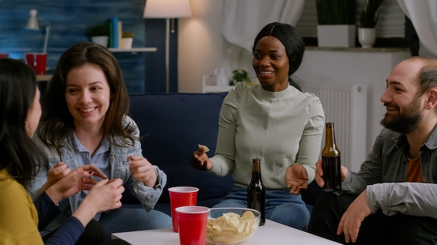 Amigos multiculturais rindo enquanto compartilham conselhos sobre estilo de vida sentados no sofá tarde da noite no livi ...
