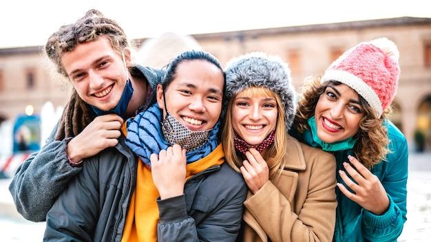 Amigos multiculturais tirando uma selfie feliz usando máscara e roupas de inverno