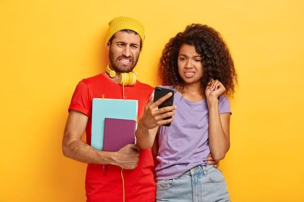 Amigos multiétínicos decepcionados olham com aversão para o dispositivo de smartphone, assistem a vídeos desagradáveis online