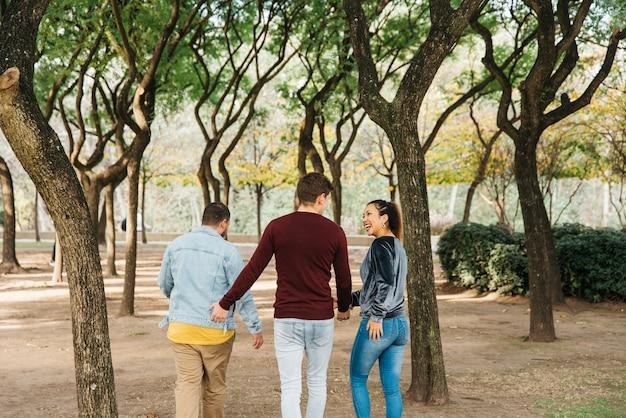 Amigos multiétnicas, rindo e andando no parque
