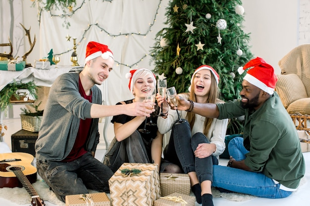 Amigos multiétnicos comemorando ano novo e brindando com taças de champanhe